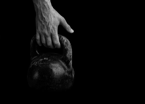 The athlete strong hand takes the kettlebell. Weight-lifting. A large sports kettlebell and an athlete arm.