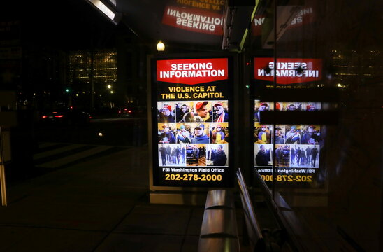 A sign at a bus stop shows people wanted by law enforcement, three days after a protest of the U.S. Congress certification of the November election results the 2020 election in Washington