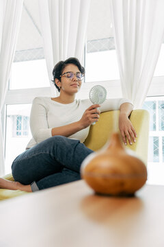 Woman sitting on her sofa with essential oil diffuser scenting her living room