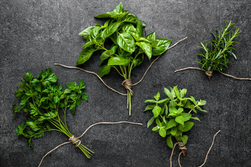 Fototapeta Bunch of fresh herbs from the garden. Mint, rosemary, parsley and basil herb on black background. obraz