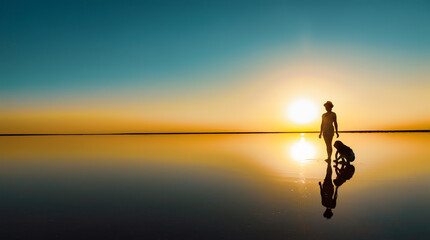Two happy lovely sisters are walking along the mirror salt lake enjoying the evening fiery sunset Fotobehang