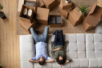 Top view of millennial couple relax on comfortable modern couch feel tired on moving day to new home. Man and woman renters or tenants rest on sofa in living room exhausted with relocation.