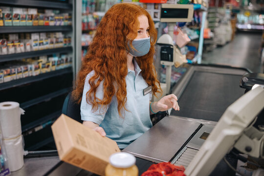 Supermarket cashier with face mask