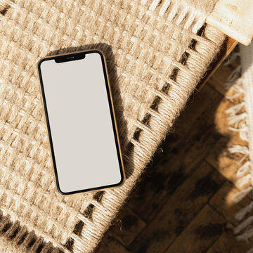 Flatlay of blank screen mobile phone on rattan chair. Flat lay, top view. Copy space mockup template. Warm sunlight shadows.