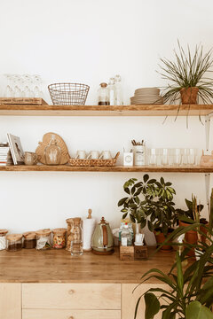 Modern boho style home kitchen interior concept. Wooden shelfs, dishes, utensils, decorations. Cozy comfortable bohemian interior design.