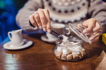 An addicted coffee lover puts a piece of white sugar in his hot drink in cafe. Concept of unhealthy diet and diabetes