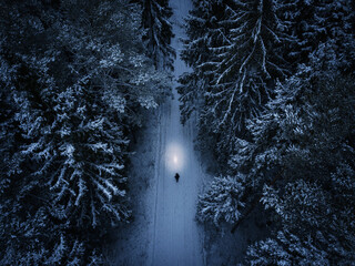 Lonely man walking through the forest during the winter night