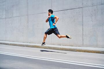Athletic man sprinting running on city street