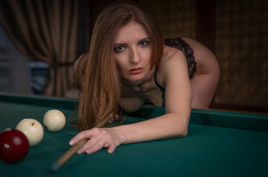 a girl in erotic lingerie sexy bent over the pool table to hit the ball with a cue