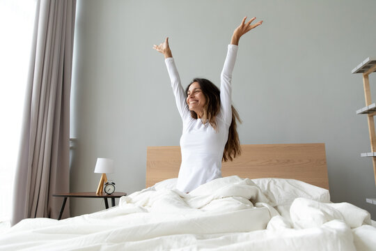 Overjoyed woman wearing pajama stretching hands after awakening, sitting in cozy bad, happy smiling attractive young female starting new day, enjoying morning after healthy sleep, doing exercises
