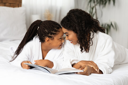 African Mom And Daughter Relaxing On Bed In Bathrobes And Reading Book