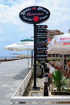 """""""We speak..."""" message in different languages (English, French, Deutch, Italian, Greek Russian, Polish etc.) at the entrance to the restaurant at Durres embankment. Durres, Albania - June 5 2019"""