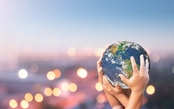 World environment day concept: Family hands holding earth global blurred city night background. Elements of this image furnished by NASA