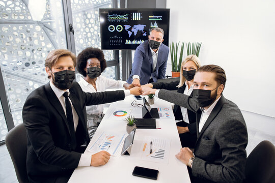 Work during covid pandemic. Happy multiethnic business people in face masks, bumping their fists as agreement and teamwork, posing to camera in modern conference room in office