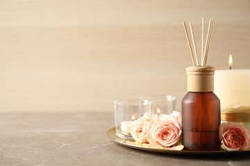 Spa composition with aroma oil and roses on grey table, space for text