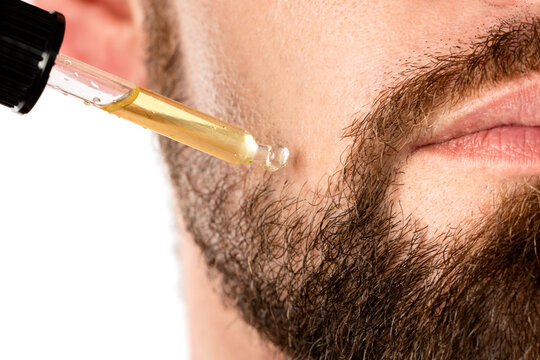 Male face and pipette with a oil for a beard growth