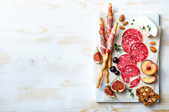 Appetizers table with italian antipasti snacks. Brushetta or authentic traditional spanish tapas set, cheese and meat variety board over wooden background. Top view, flat lay