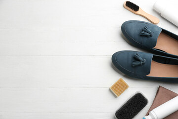Stylish footwear with shoe care accessories on white wooden table, flat lay. Space for text
