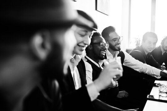 Group of handsome retro well-dressed man gangsters spend time at club, sitting and drinking whiskey. Multiethnic male bachelor mafia party in restaurant.
