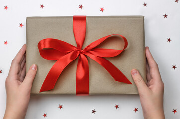 Hands holding wrapped gift box with red ribbon as a present for celebration.