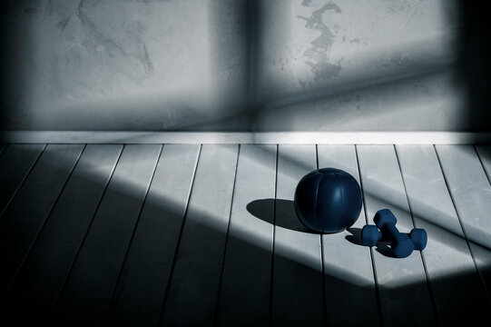 Blue medicine ball and blue bumbbells on wooden floor. Sport at home concept