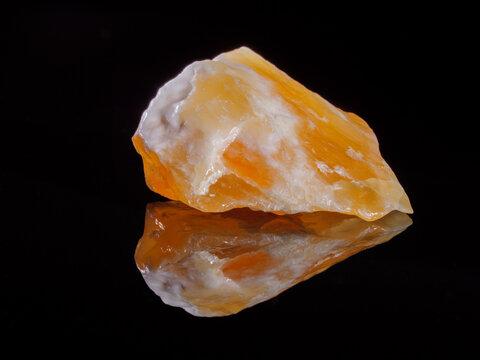 Calcite orange close-up. Black background. Macro image.