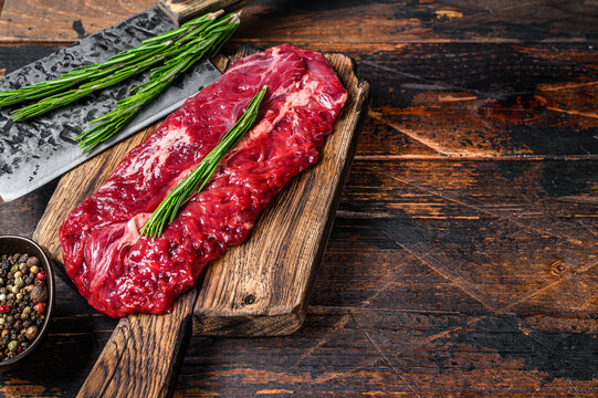 Butchers choice raw steak Onglet  Hanging Tender beef meat on a cutting board. Dark wooden background. Top view. Copy space