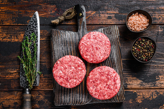 Raw steak burgers patties with ground beef and thyme on a wooden cutting board. Dark Wooden background. Top view