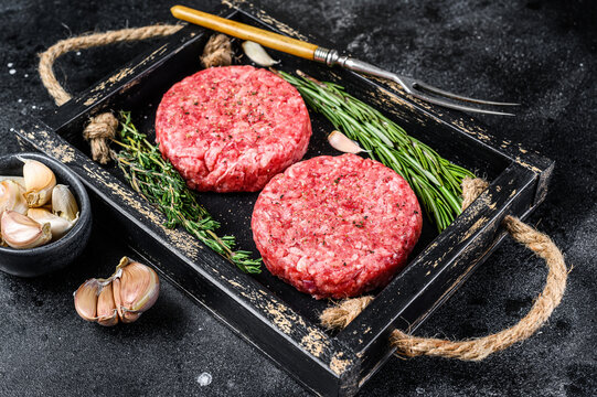 Raw beef meat patties for burger from ground meat and herbs on a wooden board. Black background. Top view
