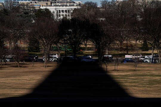 The shadow of the Washington Monument points toward the White House in Washington