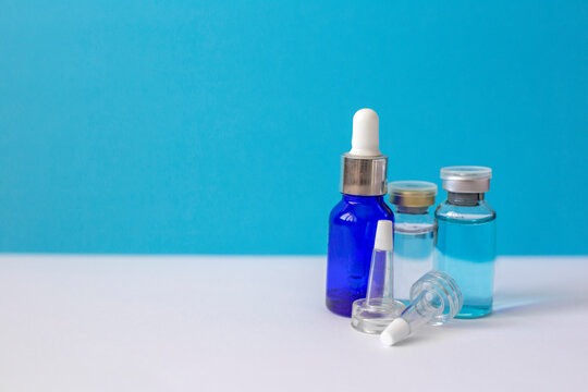 Glass bottles with hyaluronic acid stand on a blue background. Anti-wrinkle remedy