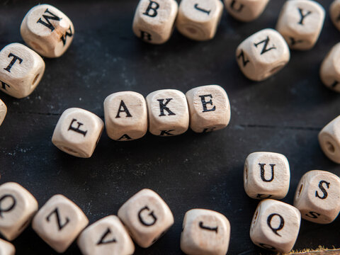 """The word """"FAKE"""" made from letter beads on a black wooden background"""