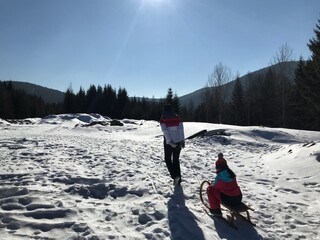 Mother Pulling Sled With Daughter On Snow Covered Field