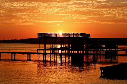 Silhouette Built Structure By Lake Against Orange Sky