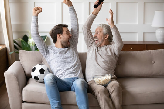 Excited millennial Caucasian man with elderly father feel euphoric celebrate win watch football game on TV together. Overjoyed adult son with mature dad triumph with team victory enjoy sports match.