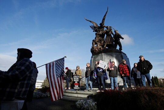 Supporters of U.S. President Donald Trump gather at the Winged Victory Monument the day before a legislative session begins in Olympia, Washington