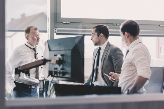 Corporate business people work in modern office. Project manager team solving a problem. Business crew discussing a business issue. Businessman looking at data at mobile phone monitor.