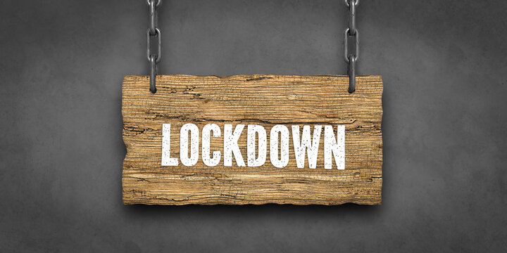 .wooden sign on chains with message LOCKDOWN in front of concrete background
