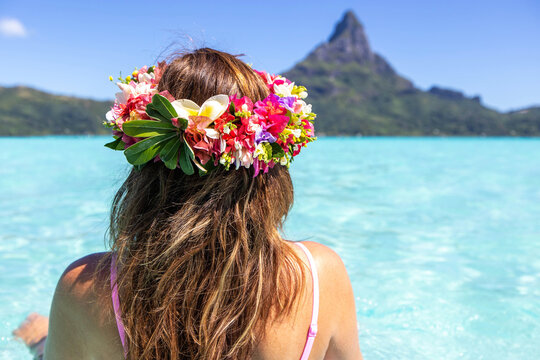 Woman wearing colorful flower crown on vacation at beautiful tropical island Bora Bora in French Polynesia