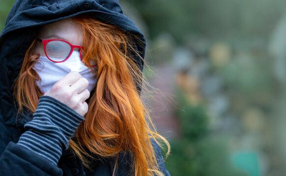 Eine Frau mit roten Haaren und Kapuze steht einsam und betrübt in einem Park. Sie trägt eine beschlagene Brille und eine Atemmaske.