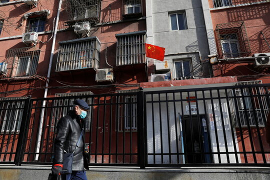 A man wearing a face mask walks past apartments with a Chinese flag, following new cases of the coronavirus disease (COVID-19) in the country, in Beijing