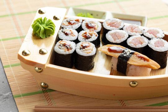 Set of maki sushi on wooden boat tray