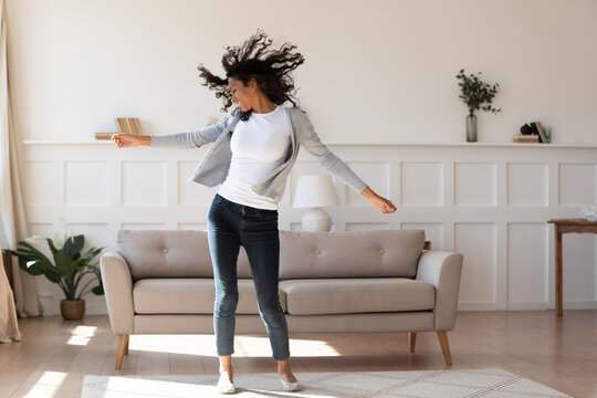 Full length young african ethnicity multiracial woman in casual wear dancing to favorite energetic audio music, having fun alone in living room, enjoying active domestic hobby pastime, feeling freedom