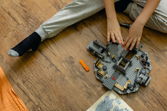 A blond boy of nine years old collects a large Lego set of the Millennium Falcon in his room. Based on the film Star Wars.