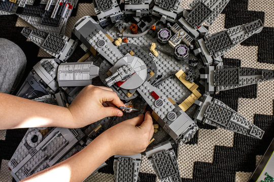 A boy of eight years old collects a Lego set Millennium Falcon according to the instructions. The spaceship Imperial Cruiser lies nearby.