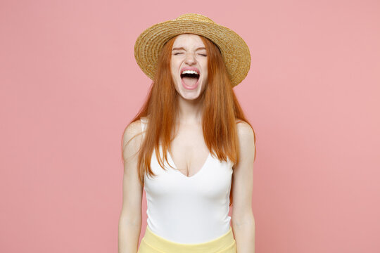 Young irritated angry hysteric stressed redhead woman 20s ginger long hair wearing straw hat summer clothes closed eyes screaming shouting isolated on pastel pink color background studio portrait