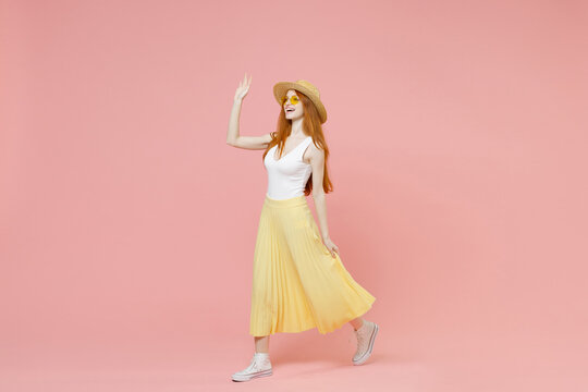 Full length body young smiling redhead ginger woman in straw hat glasses summer clothes maxi skirt walk going waving hand greet someone look aside isolated on pastel pink background studio portrait
