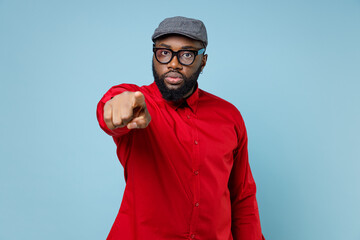 Displeased strict young bearded african american man 20s wearing casual red shirt eyeglasses cap standing pointing index finger on camera isolated on pastel blue color wall background studio portrait.