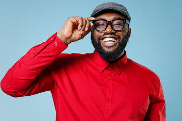Close up of laughing cheerful young bearded african american man 20s wearing casual red shirt cap eyeglasses standing and looking camera isolated on pastel blue color wall background studio portrait.