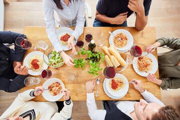 Freunde bei gemeinsamer Pasta Mahlzeit mit Tomatensauce und frischem Basilikum